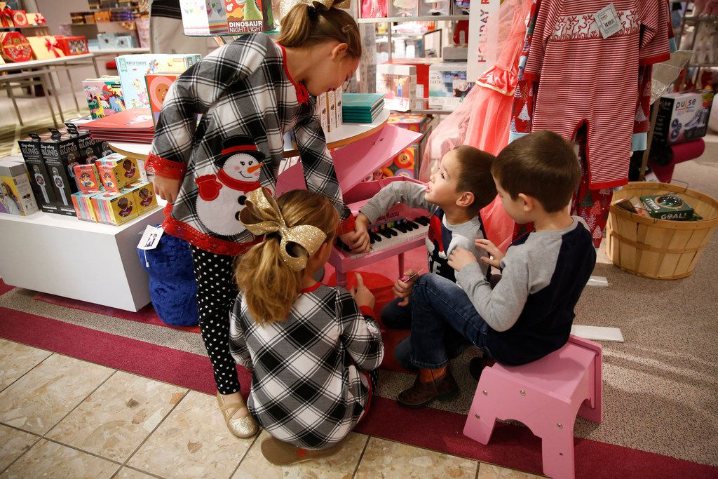 Abby Miller, 8, with her twin Allie and her brothers Colin and Hunter Miller, 5, play with a toy piano at Neiman Marcus in the NorthPark Center in Dallas on Nov. 23, 2018. (Nathan Hunsinger/The Dallas Morning News)