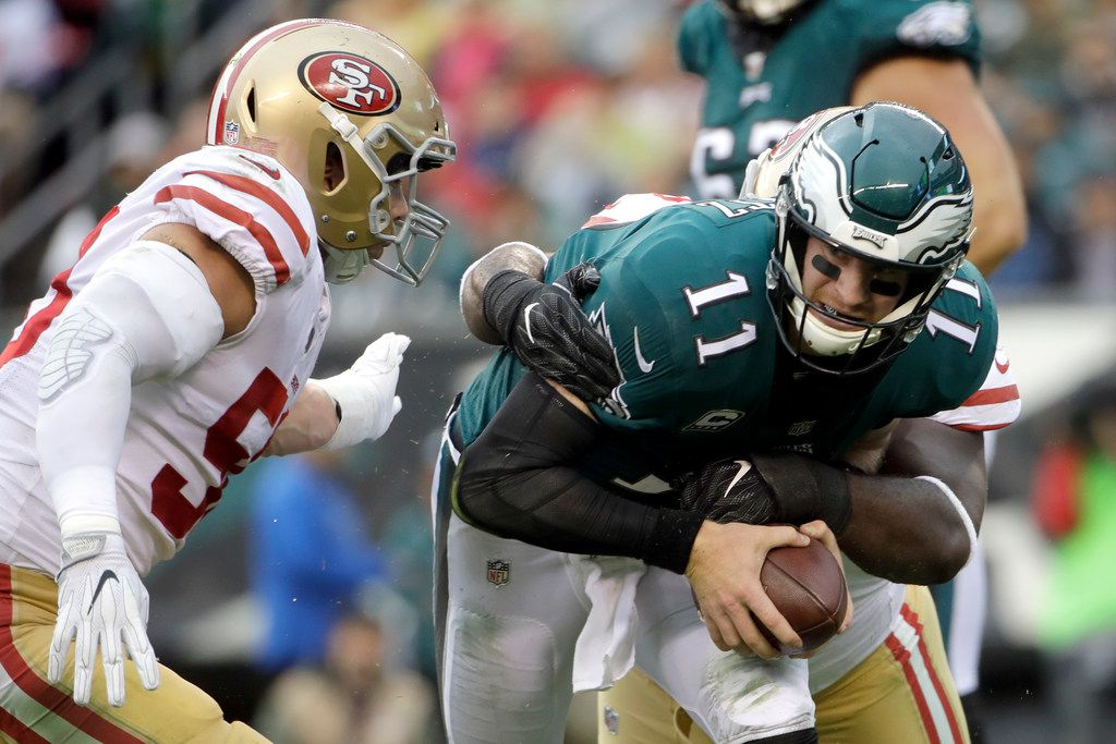 Philadelphia Eagles' Carson Wentz (11) is tackled by San Francisco 49ers' Earl Mitchell (90) and Brock Coyle (50) during the first half of an NFL football game, Sunday, Oct. 29, 2017, in Philadelphia. (AP Photo/Michael Perez)