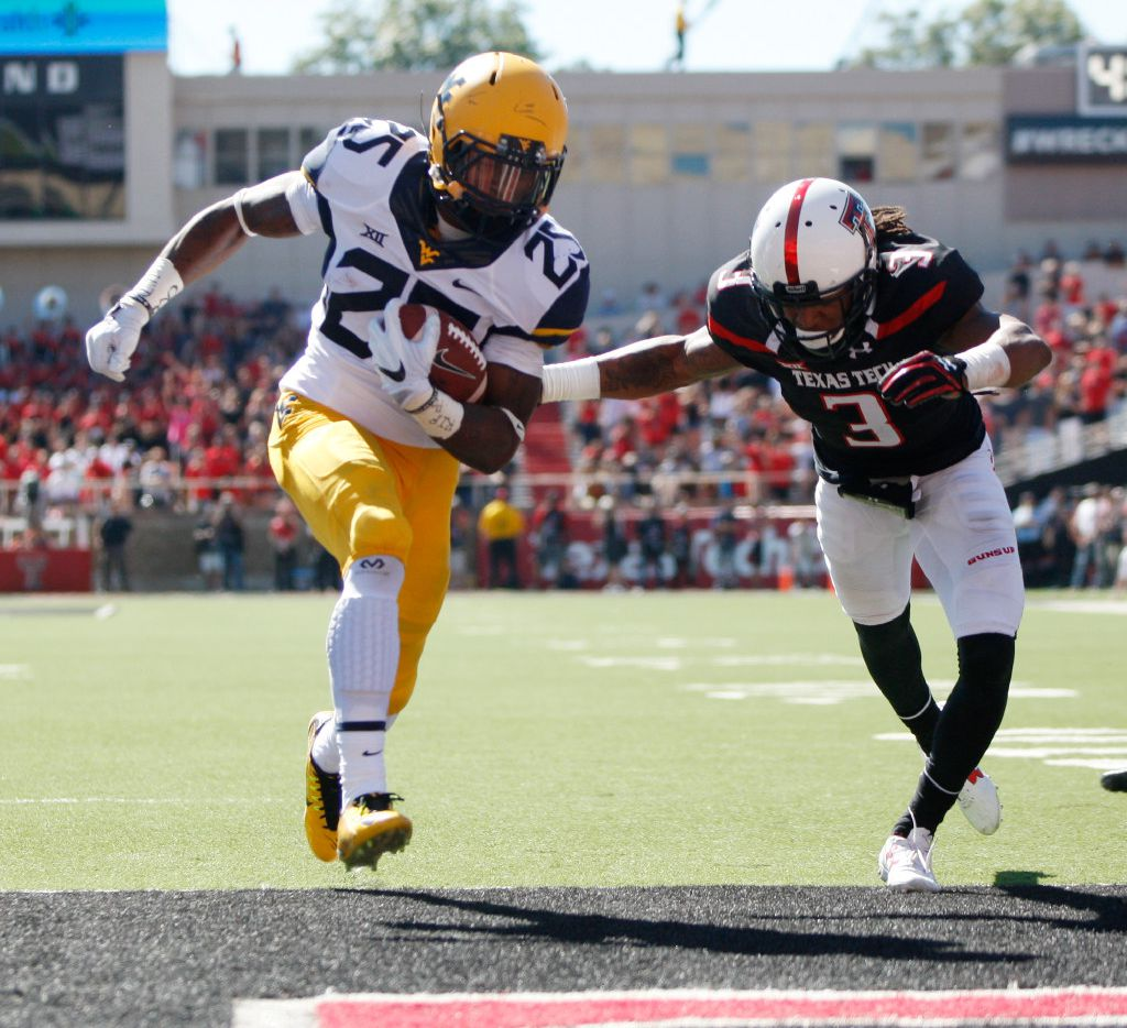 West Virginia running back Justin Crawford scores a touchdown pastTexas Tech defensive back D.J. Polite-Bray during the first half of an NCAA college football game Saturday, Oct. 15, 2016, at Jones AT&T Stadium  in Lubbock, Texas. (Mark Rogers/Lubbock Avalanche-Journal via AP)