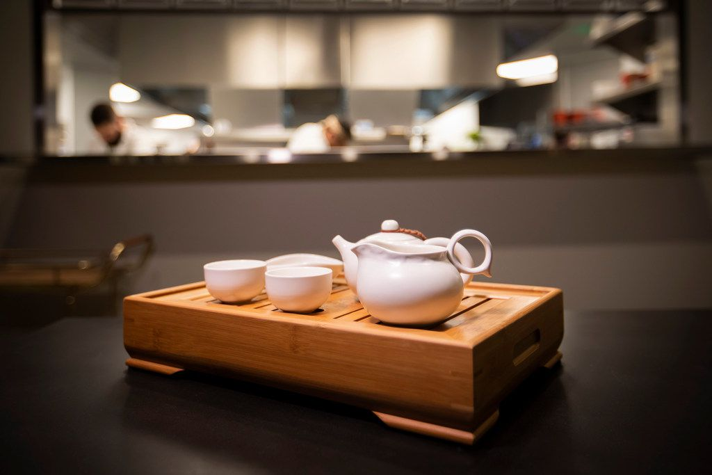 """During tea service at Fine China, servers """"bloom"""" the tea by pouring out the first bit of hot tea into the slats of a hollow wooden box."""