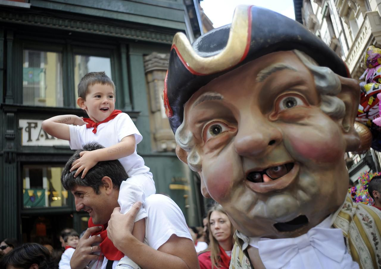 Cabezudos (Big-Heads) chase parents and children in the crowds during the children's parade.