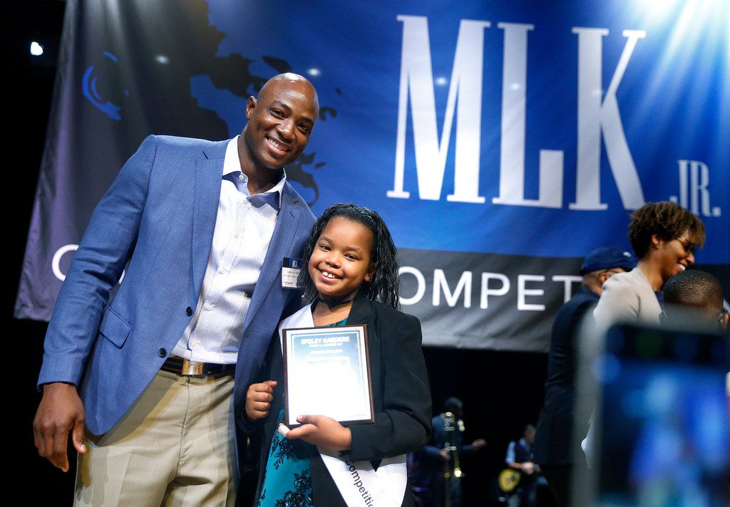 Jasira King, a fourth grader at William Brown Miller Elementary School poses for family photos with judge and former Dallas Cowboys football player DeMarcus Ware after her winning speech before an audience at W.H. Adamson High School in Dallas, Thursday, January 17, 2019. In celebration of Martin Luther King Jr.'s legacy, fourth and fifth-grade students at Dallas ISD elementary schools competed in the final round of the 27th Annual Foley Gardere MLK Jr. Oratory Competition