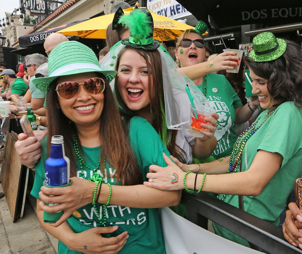 Friends pose as they enjoy beverages in the patios of restaurants along Greenville Avenue during the block party at the Dallas St. Patrick's Parade & Festival along Greenville Avenue in Dallas on Saturday.