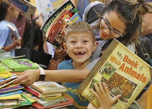 Daniel Smith de cinco años de edad está emocionado de recibir nuevos materiales de lectura gratuitos. Su mamá Yaneth Garcia lo llevó a la feria de regreso a clases del alcalde, el viernes. (Por LOUIS DELUCA/DMN)