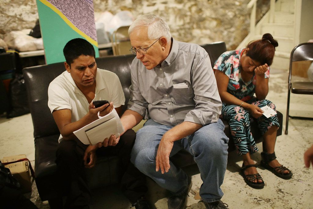 Ruben Garcia, center, director of the Annunciation House in El Paso,  speaks on a cell phone with a person from the Office of Refugee Resettlement. Garcia said shelters in West Texas and New Mexico are filled to capacity with record number of families from Central America.
