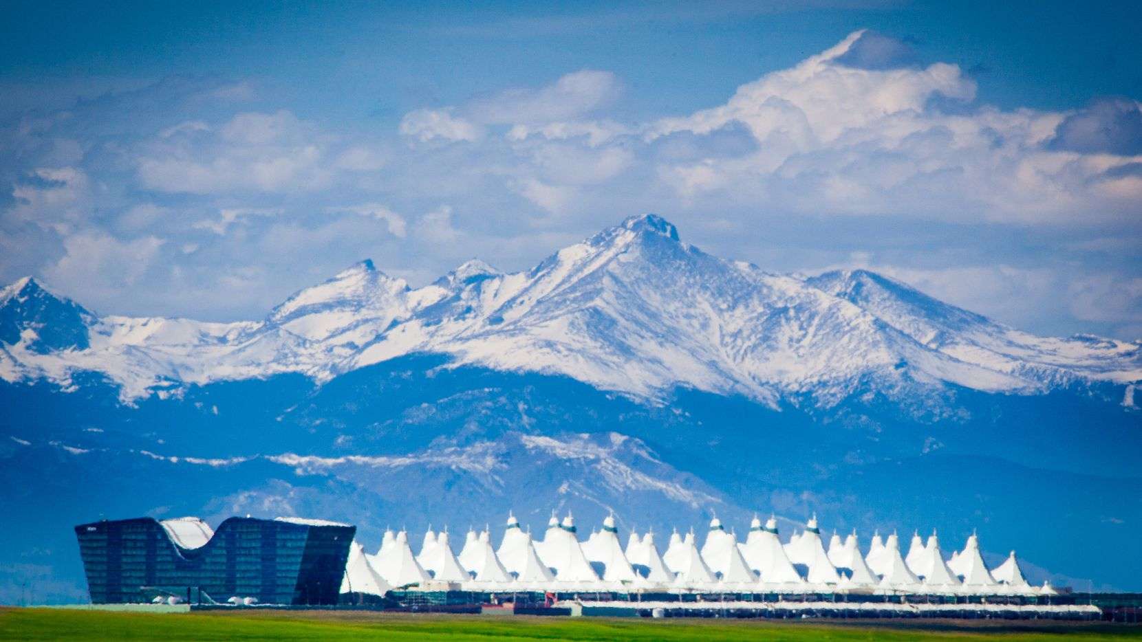 The Jeppesen Terminal at Denver International Airport with the Rocky Mountains behind it.