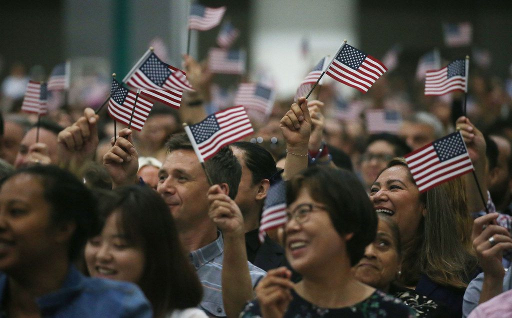 People wave American flags at a naturalization ceremony on July 25, 2018 in Los Angeles, California.