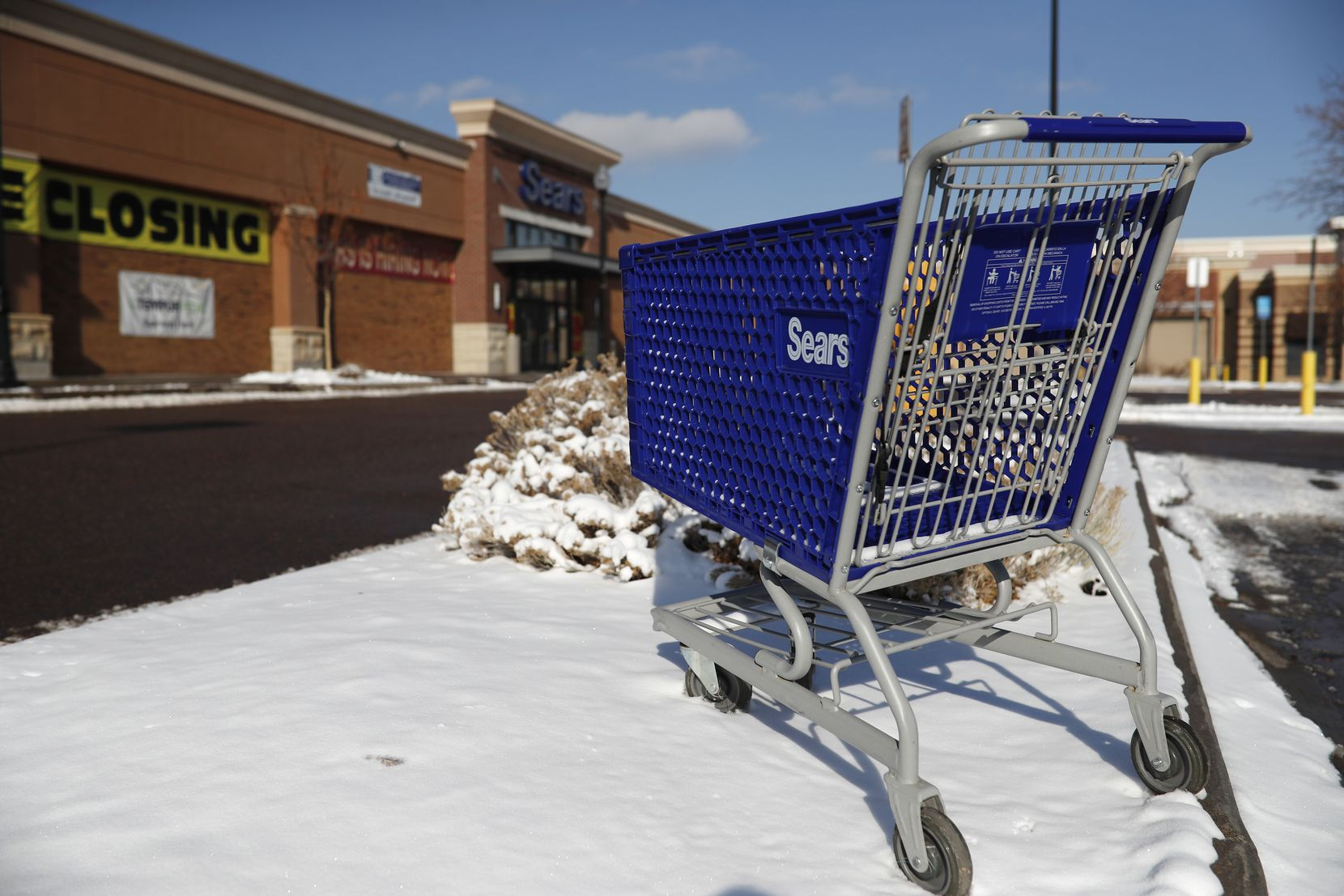 In this Jan. 1, 2019, file photo, an empty shopping cart sits outside a Sears store in the Streets of Southglenn mall in Littleton, Colo.