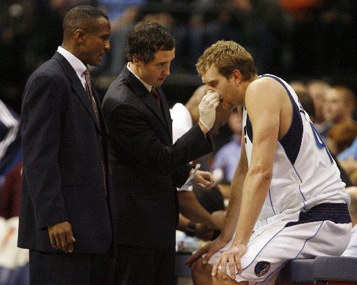 Dallas Mavericks assistant coach Dwane Casey (left) watches as forward Dirk Nowitzki is attended to after suffering a bloody nose from a foul during the second half of Dallas' 107-100 win over the Minnesota Timberwolves December 30, 2008 at the American Airlines Center in Dallas. (G.J. McCarthy / The Dallas Morning News)