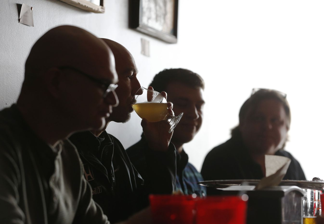 Darrell Caldwell (second from left)  drinks beer and eats with Ernest Adams (left), Jared Holeyfield (second from right) and Tony Jenkins (far right) at Austin Beer Garden Brewing Company.