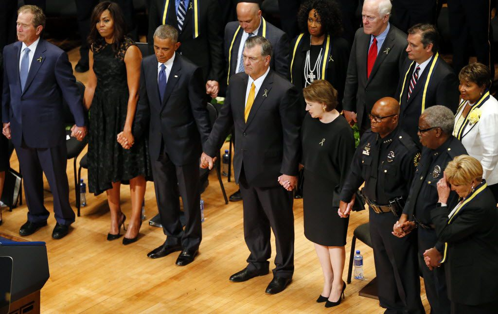 From left, former President George W. Bush, first lady Michelle Obama, President Barack Obama, Dallas Mayor Mike Rawlings, wife Micki Rawlings, Dallas Police Chief David Brown, DART Police Chief J.D. Spiller and Fort Worth Mayor Betsy Price joined hands at the end of an interfaith memorial service for five fallen officers at the Morton H. Meyerson Symphony Center in Dallas on July 12, 2016. (Tom Fox/The Dallas Morning News)