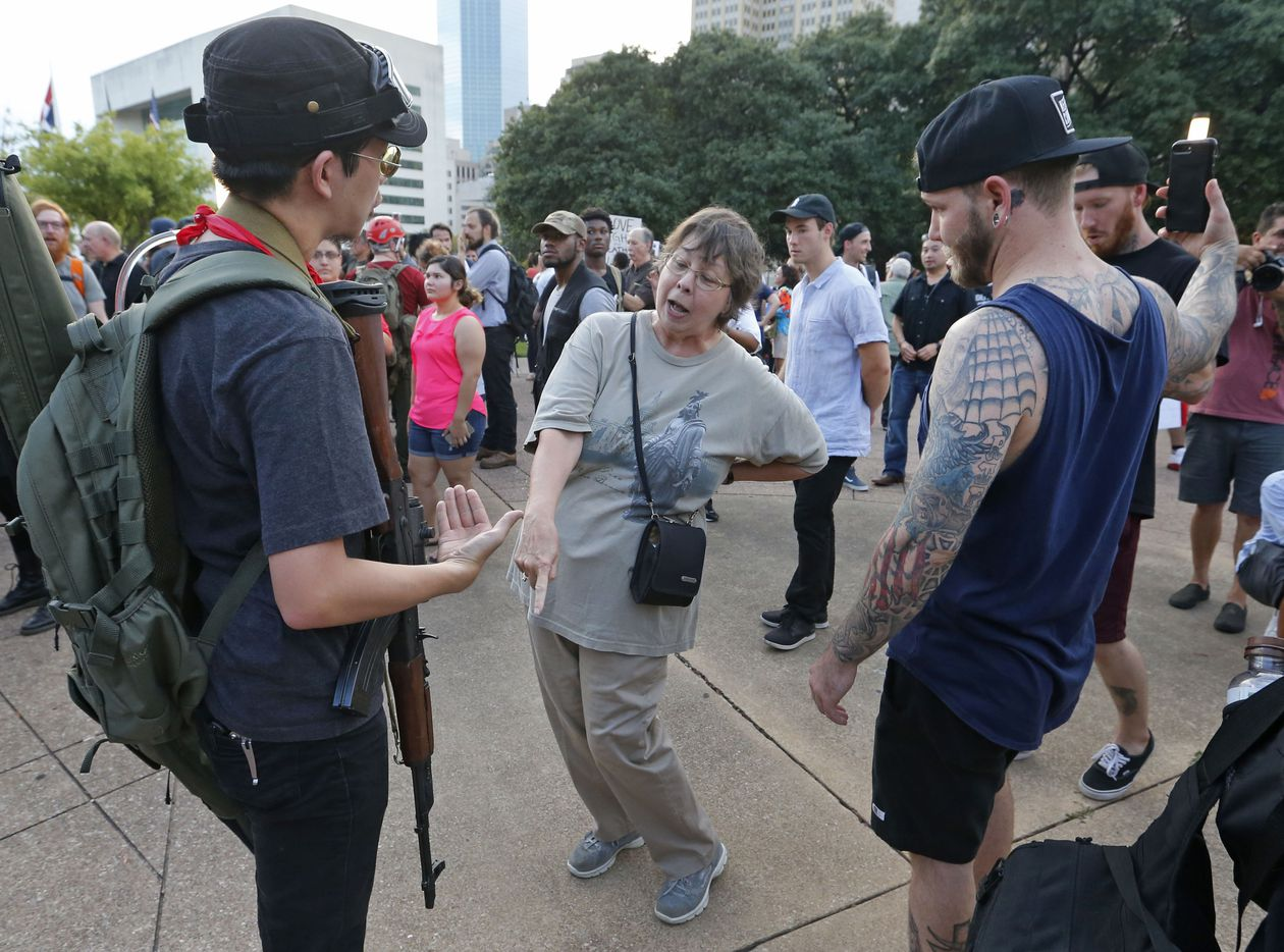 Patricia Viveros confronts a rifle-carrying protestor on City Hall Plaza during the March Against White Supremacy.