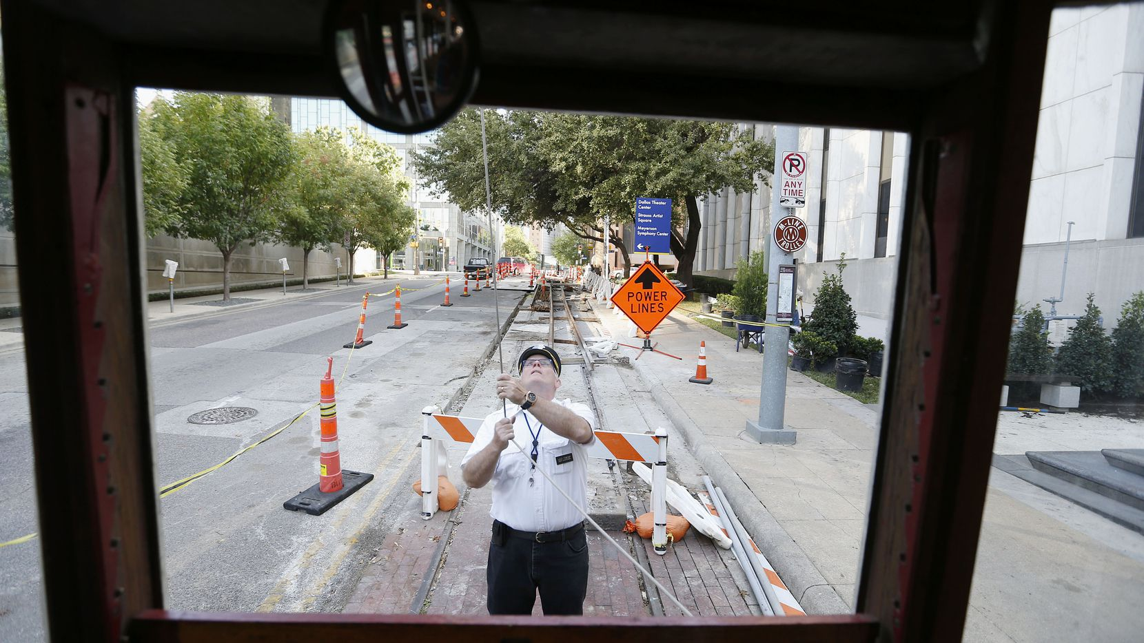 """M-Line Trolley motorman Leo Tresp switches the ends of the vehicle's cable at the route's southern terminus along St. Paul Street near Ross Avenue in Dallas Wednesday October 30, 2014. Currently under construction behind Tresp, an extension of the streetcar system will include parts of downtown Dallas, but operated by Dallas Area Rapid Transit (DART). On Wednesday, Tresp operated a vehicle built in 1913, called the """"Green Dragon."""" Tresp has been a motorman for eight years, but also serves as the chief training officer and assistant dispatcher for the McKinney Avenue Transit Authority. (Andy Jacobsohn/The Dallas Morning News) 11012014xNEWS"""
