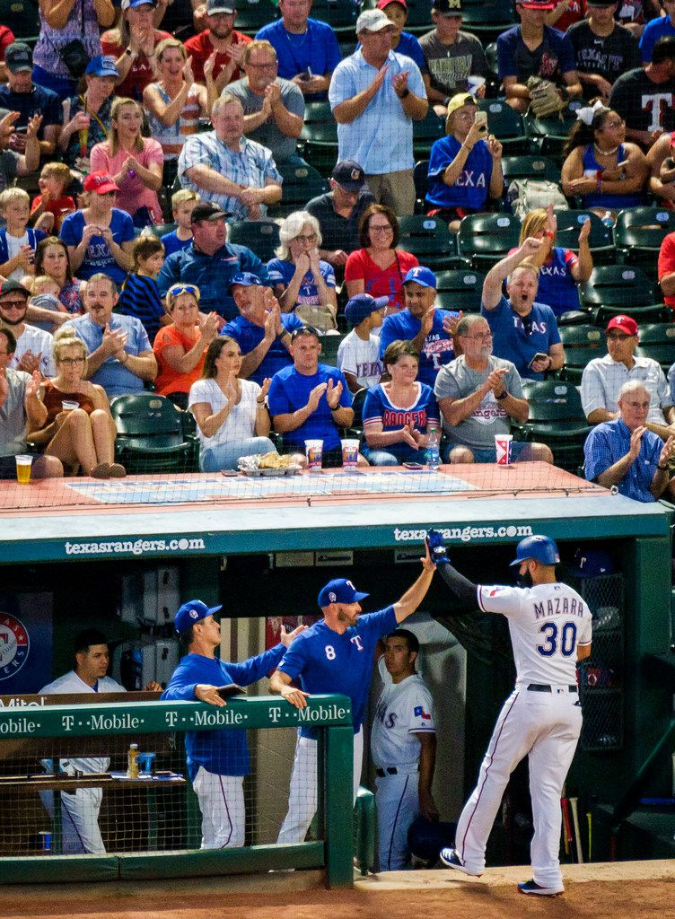 Texas Rangers right fielder Nomar Mazara (30) gets a hand from manager Chris Woodward after scoring during the first inning against the Tampa Bay Rays at Globe Life Park on Wednesday, Sept. 11, 2019, in Arlington. (Smiley N. Pool/The Dallas Morning News)