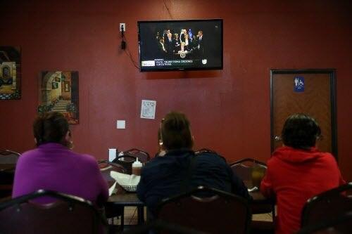 Tres mexicanas, que pidieron no ser identificadas, observan al presidente Donald Trump firmar una órden ejecutiva que  activa la construcción de un muro en la frontera con México. (Rose Baca/The Dallas Morning News)