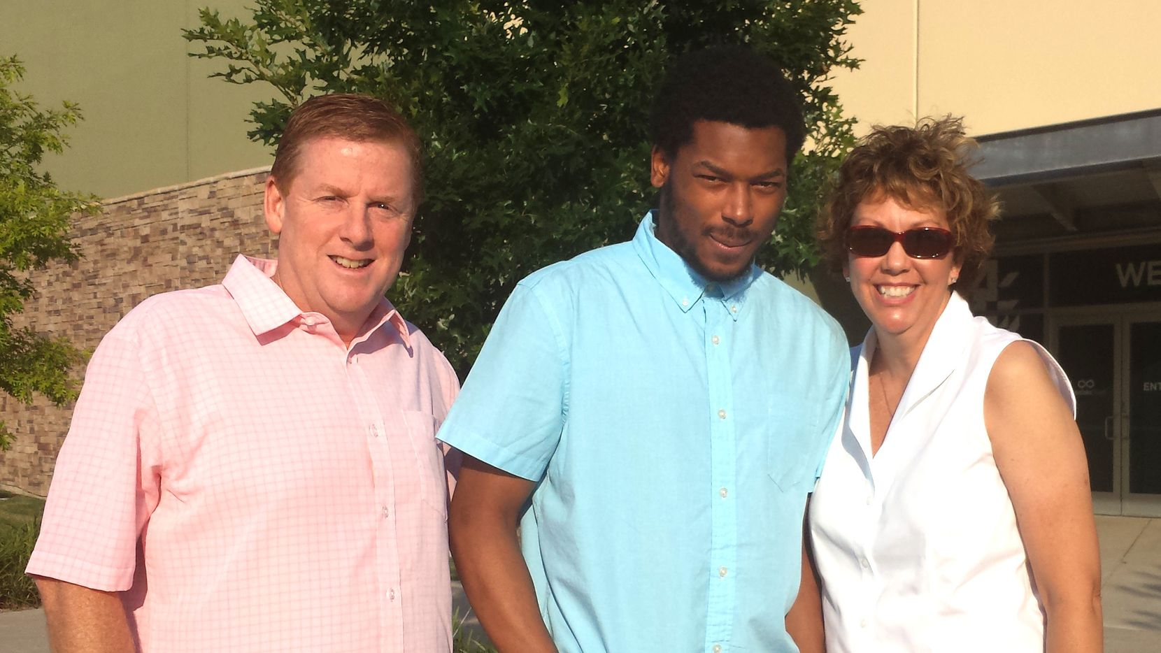 Dave and Lisa Stephenson pose with Thomas Johnson at their church in Plano in July 2014. Thomas Johnson, former Skyline and Texas A&M football star stayed as a guest in their home. Dave and his wife tried to rehabilitate Johnson before the murder of David Stevens while he was running at White Rock Lake on Oct. 12, 2015. (Photo Courtesy of Stephenson Family)