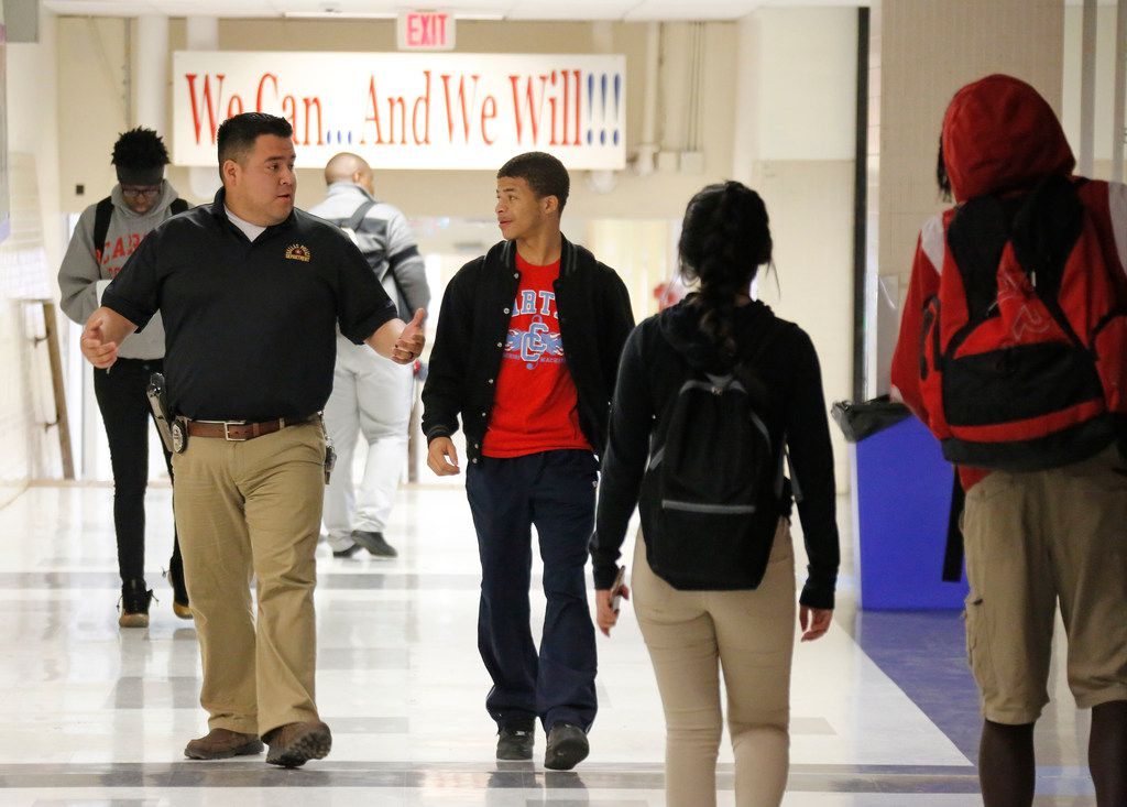 Dallas Police Officer Victor Guardiola (left) talks with Carter High School student Sedric Owens on Dec. 13, 2018, as part of a mentoring program at the school. Sedric says the mentorship program is important to him, especially after his father died..