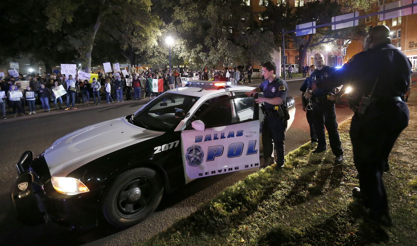 Dallas Police officers gather near protesters against President-elect Donald Trump on Elm Street in downtown Dallas, Thursday, Nov. 10, 2016.