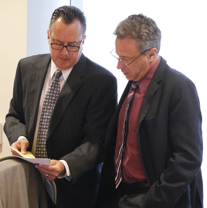 Board member Rick Salinas (left) talked to George Tomasovic, chairman of the board of the Dallas Police and Fire Pension System, during an August meeting.
