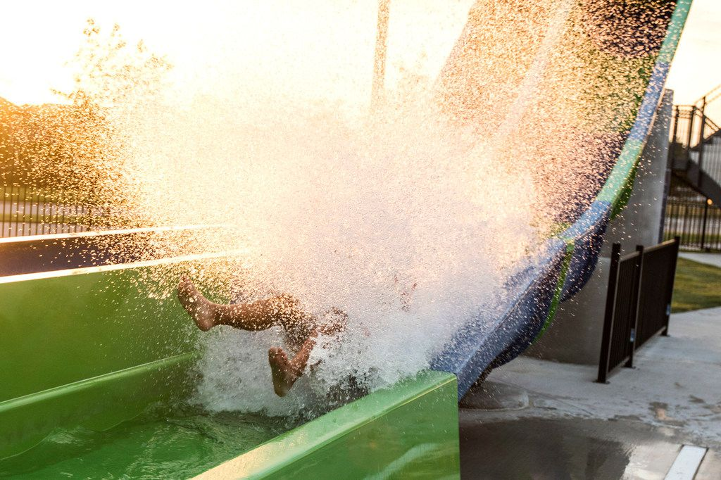 Ashtin Majacot, 11, of McKinney, splashes into water while riding a slide during a pool party in McKinney on Saturday.