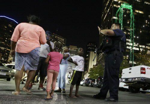 Un policía desvía a transeúntes en el centro de Dallas luego que oficiales resultaran heridos y al menos cuatro fallecieran el jueves 7 de julio. (LM Otero/AP)