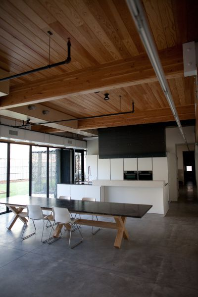 Douglas-fir beams, concrete floors and exposed ductwork give the 4,410-square-foot interior a loft feel. The balcony's Plexiglass half-wall allows light from the street-facing window to wah upstairs and down. The Buchanan-designed stone table will soon be joined by the rest of the family's furniture.
