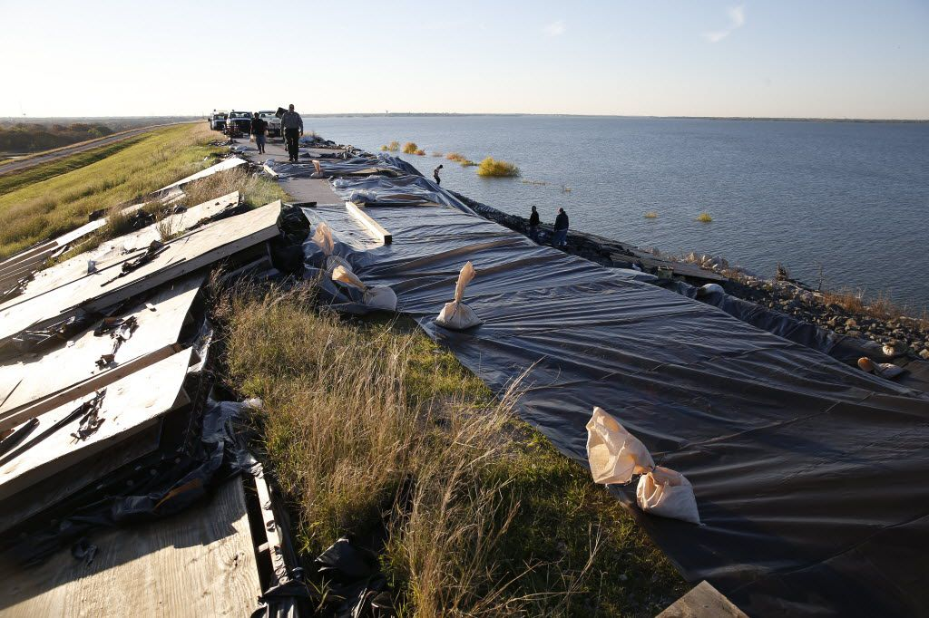 Workers  used tarps and sandbags to temporarily prevent further erosion after a 160-foot long landslide (right) was caused by rain water flowing into cracks at the crest of the dam at Lewisville Lake.