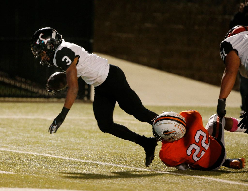 Trinity running back Zechariah Moore (3) scores a touchdown as he is tackled by Haltom's Johnny Smith-Rider (22) during the first half of their high school football game on Oct. 11, 2019 in North Richland Hills. (Michael Ainsworth/Special Contributor)