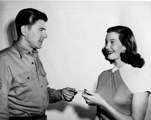 In this March 30, 1947 picture, Lois Maxwell, 20-year-old Canadian-born actress, receives her Screen Actors Guild member card from the new president of the guild, actor Ronald Reagan, in Hollywood, Calif. (AP Photo)