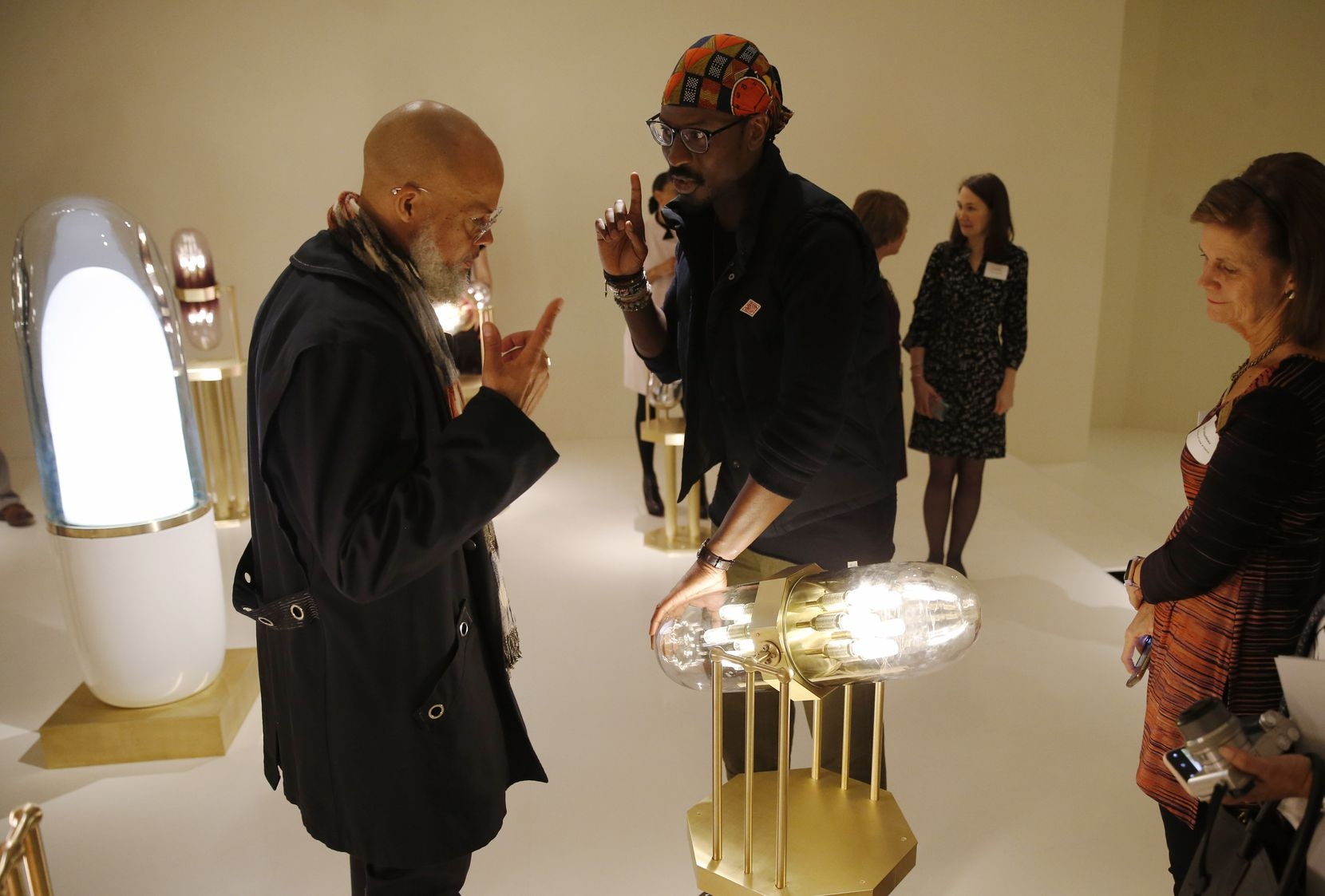 """Artist Ini Archibong (center) explains how his piece called """"theoracle"""" works to Jackson (left, who goes by one name) during a preview event for """"Speechless: Different by Design"""" on Tuesday, Nov. 5, 2019."""