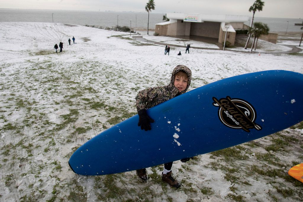 Ben Platt caries a surf board up a hull at Cole Park after sledding down it flowing a night of snow fall in Corpus Christi, Texas, on Friday, Dec. 8, 2017.