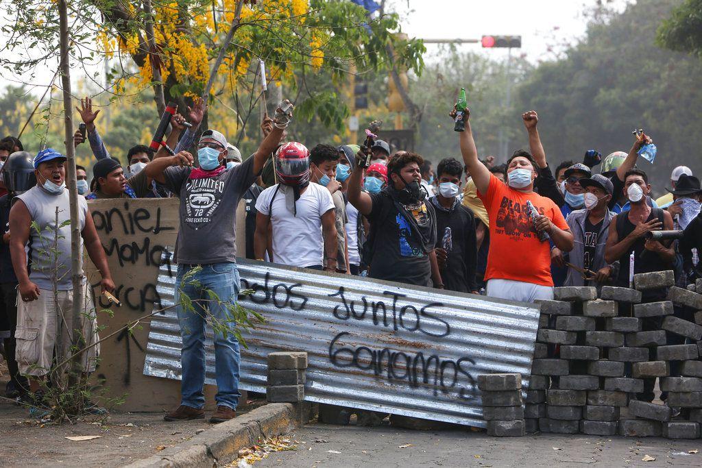 Un grupo de manifestantes lanza consignas tras bloquear una calle en un confrontamiento con las fuerzas de seguridad cerca de la Universidad Politécnica de Nicaragua (UPOLI) en Managua, Nicaragua, el sábado 21 de abril de 2018. (AP Foto/Alfredo Zúñiga)