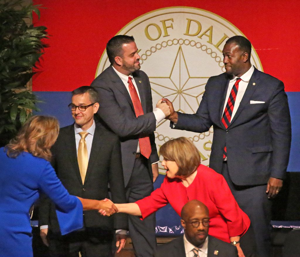 Dallas City Council's Adam McGough and Casey Thomas II shake hands, as do Jennifer S. Gates and Sandy Greyson, front, as Scott Griggs looks on after the Dallas City Council is sworn in at a ceremony at the Morton H. Meyerson Symphony Center in Dallas on June 19, 2017.