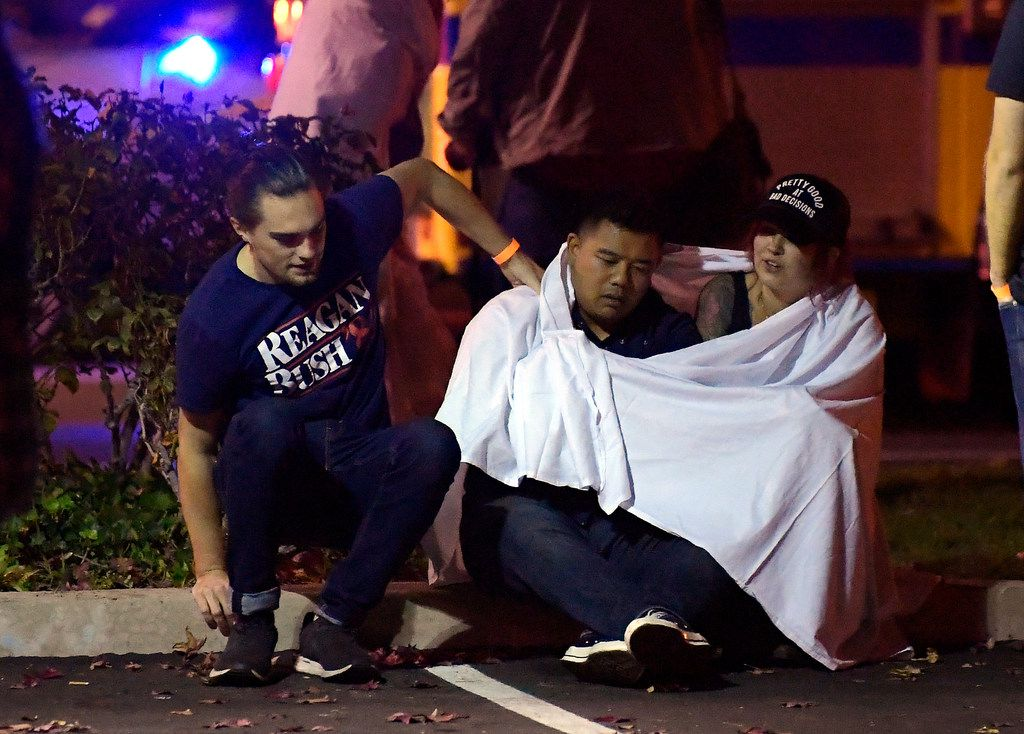 "People comfort each other as they sit near the scene Thursday, Nov. 8, 2018, in Thousand Oaks, Calif. where a gunman opened fire Wednesday inside a country dance bar crowded with hundreds of people on ""college night,"" wounding 11 people including a deputy who rushed to the scene. Ventura County sheriff's spokesman says gunman is dead inside the bar."