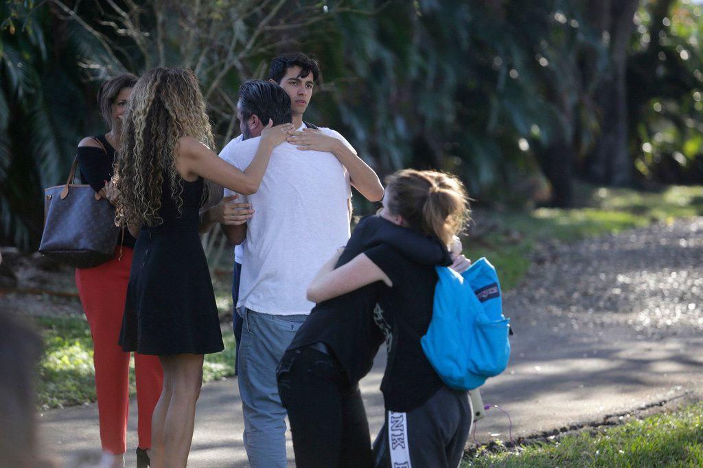 Parents and students gather outside the Marjory Stoneman Douglas High School during a shooting incident in Parkland, Fla.