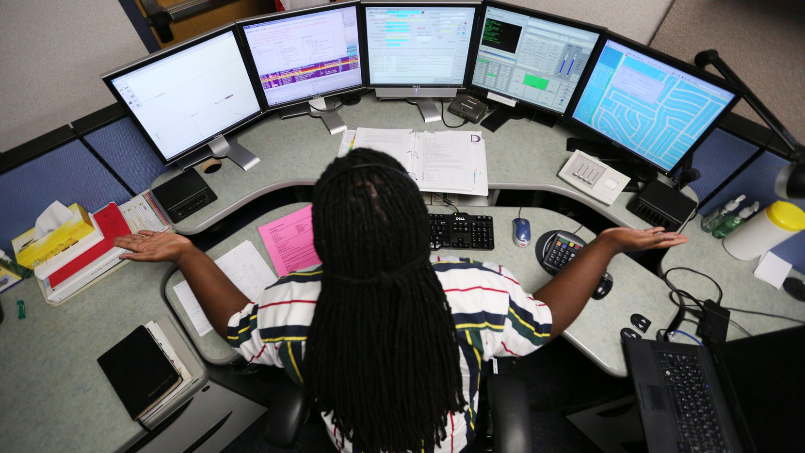 Ward Hughes of Irving reacts to a 911 caller inside the dispatch center on the lower level in Plano Municipal Center in Plano.