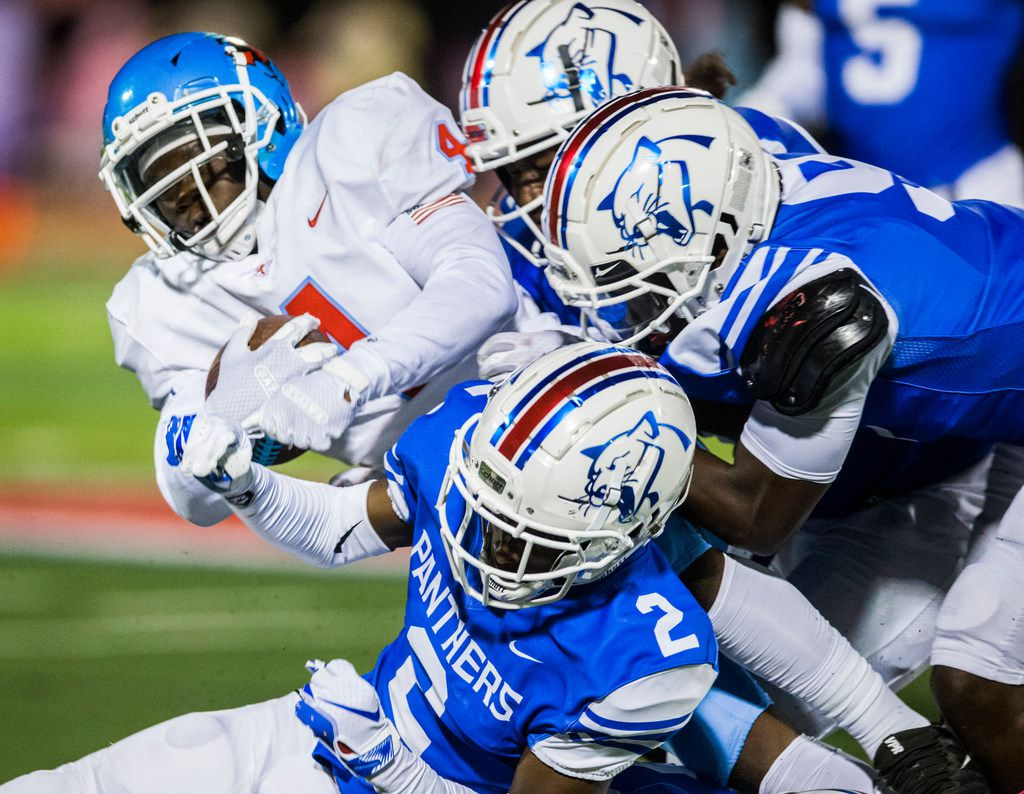 Skyline running back Qualon Farrar (4) is tackled by Duncanville defenders during the first quarter of a high school football game between Skyline and Duncanville on Friday, October 4, 2019 at Panther Stadium in Duncanville. (Ashley Landis/The Dallas Morning News)
