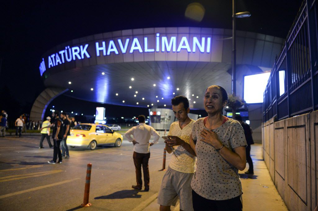 People stand outside Istanbul's Ataturk airport, Tuesday, June 28, 2016. Two explosions have rocked Istanbul's Ataturk airport, killing several people and wounding others, Turkey's justice minister and another official said Tuesday. A Turkish official says two attackers have blown themselves up at the airport after police fired at them. The official said the attackers detonated the explosives at the entrance of the international terminal before entering the x-ray security check. Turkish authorities have banned distribution of images relating to the Ataturk airport attack within Turkey.