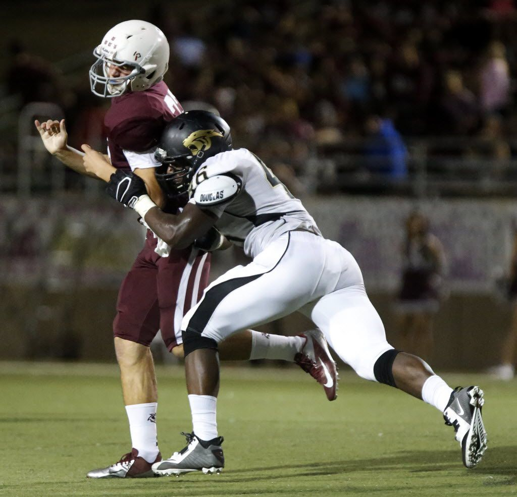 (TXHSFB) Plano East defensive lineman Landis Durham (46) pressures Plano quarterback Quinn Waterbury (22) in the second quarter as Plano High School played Plano East High School at Clark Stadium in Plano on Friday night, October 10, 2014.  (Stewart F. House/Special Contributor)