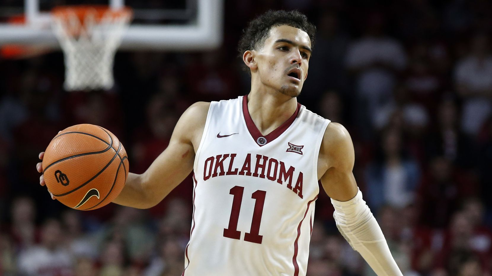 FILE - In this Feb. 17, 2018, file photo, Oklahoma guard Trae Young (11) brings the ball upcourt during the second half of an NCAA college basketball game against Texas in Norman, Okla.  (AP Photo/Sue Ogrocki, File)