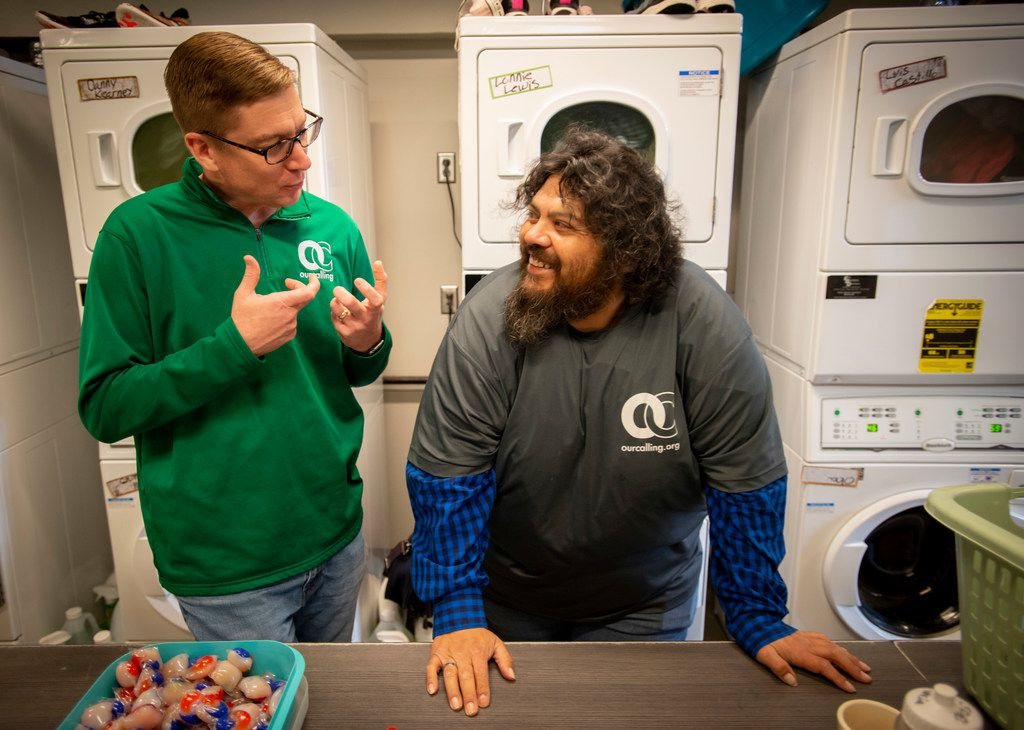 Wayne Walker talks with volunteer John Garcia who works doing laundry for homeless people at Our Calling on April 23, 2019 in Dallas.