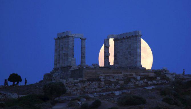 La Luna llena se levanta detrás del antiguo templo de Poseidon en cabo de Sunión, a unos 65 kilómetros (40 millas) al sur de Atenas, el viernes 27 de julio de 2018. El viernes tuvo lugar el eclipse lunar más largo del siglo y fue visto en distintas latitudes. (AP Foto/Thanassis Stavrakis)