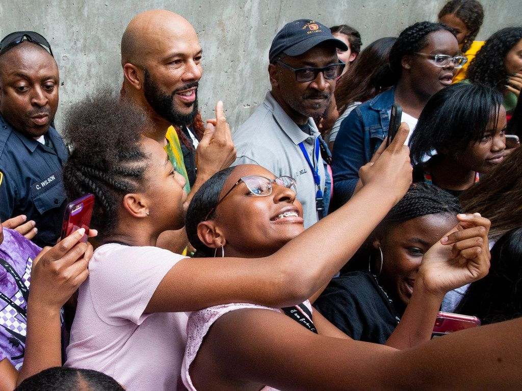 Students take pictures with rapper Common at Booker T. Washington High School for the Performing and Visual Arts in Dallas on Wednesday, August 28, 2019. (Shaban Athuman/Staff Photographer)