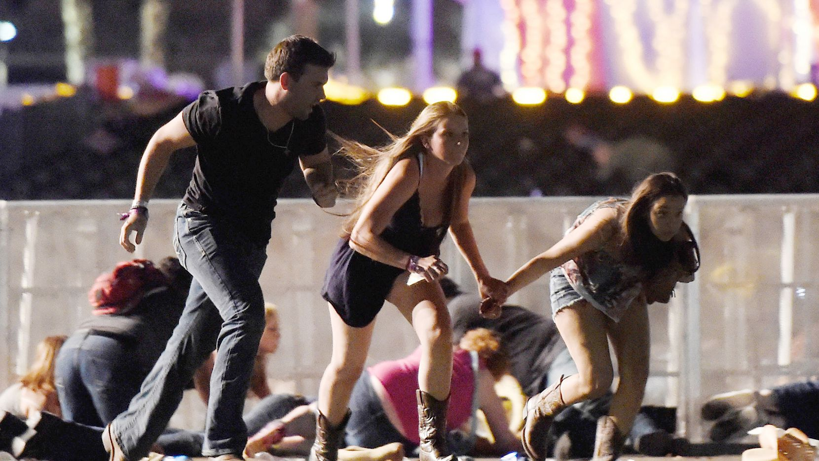 People run from the Route 91 Harvest country music festival after apparent gun fire was heard on October 1, 2017 in Las Vegas, Nevada. A gunman has opened fire on a music festival in Las Vegas, leaving at least 58 people dead and more than 500 injured. Police have confirmed that one suspect has been shot.