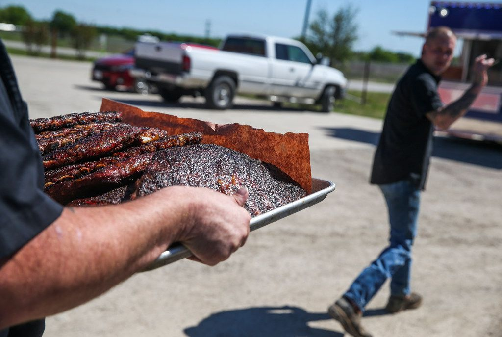 Chad Sessions, left, and Anthony Potter transport meats from the smoker at Smoke Sessions Barbecue on Friday, April 20, 2019 in Royse City, Texas. (Ryan Michalesko/The Dallas Morning News)