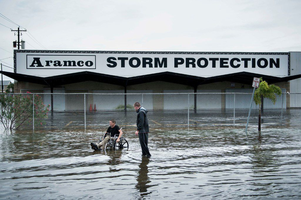 Brad Matheney offers help to a man in a wheelchair in a flooded street while Hurricane Henry passes through Texas August 26, 2017 in Galveston, Texas. Hurricane Harvey left a trail of devastation Saturday after the most powerful storm to hit the US mainland in over a decade slammed into Texas, destroying homes, severing power supplies and forcing tens of thousands of residents to flee.