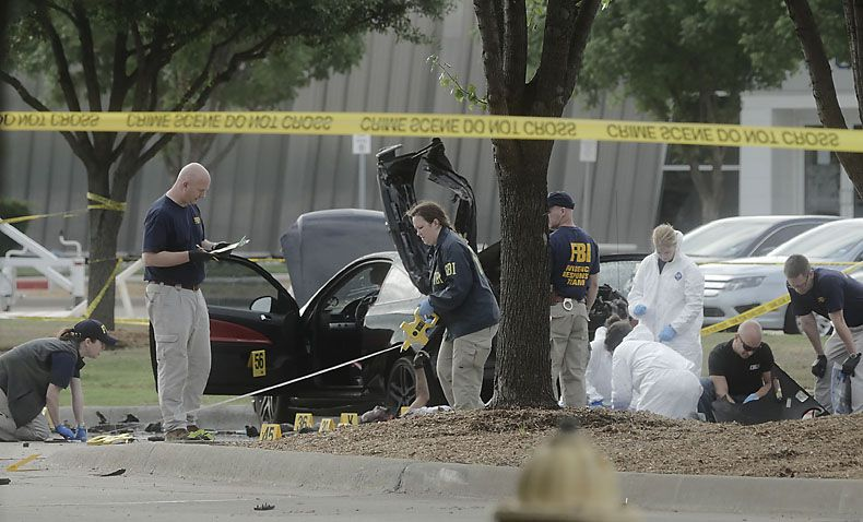 FBI agents collect evidence around the car driven by two men killed Sunday when they opened fire outside a contest for cartoons depicting the Muslim prophet Mohammad at Garland ISD's Culwell Center.