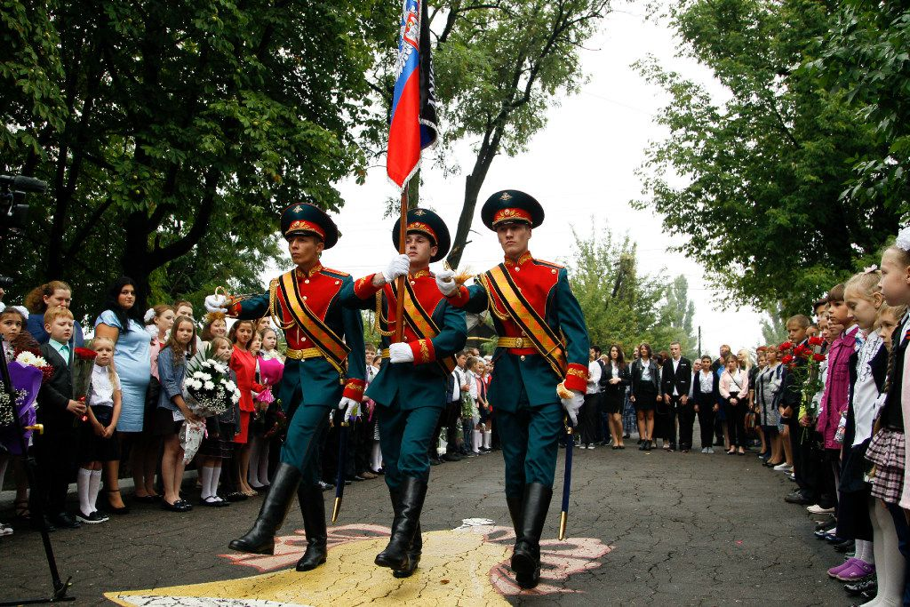 Schoolchildren watch as servicemen carry a flag of the Russia-backed self-proclaimed separatist Donetsk republic, at a ceremony on the first day of school in Donetsk, Ukraine, Friday, Sept. 1, 2017. Ukrainian government and pro-Russia separatists in eastern Ukraine have agreed to a cease-fire last month to help reduce tensions as the new school year starts Sept. 1, but the deal has been repeatedly violated.
