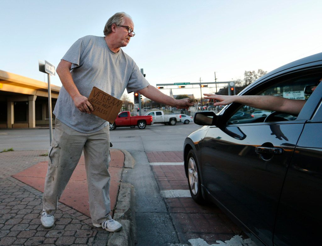 Scott Randall panhandles at the intersection of Walnut Hill Lane and Central Expressway in Dallas on Monday, February 26, 2018.