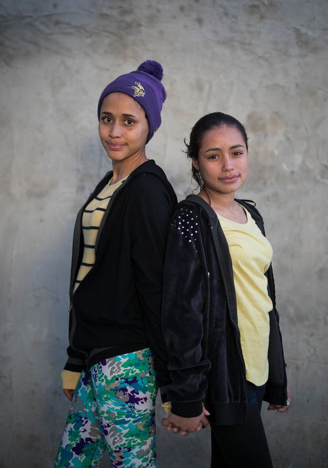 In this Feb. 6, 2019 photo, El Salvador migrant sisters 15-year-old Milagro de Jesus Henriquez Ayala, left, and Xiomara, 13, pose for a portrait at the Agape World Mission shelter in Tijuana, Mexico. The girls say they are too afraid to cross the border illegally after seeing the towering wall topped with concertina wire, especially since Milagro is nearly six months pregnant. (AP Photo/Emilio Espejel)